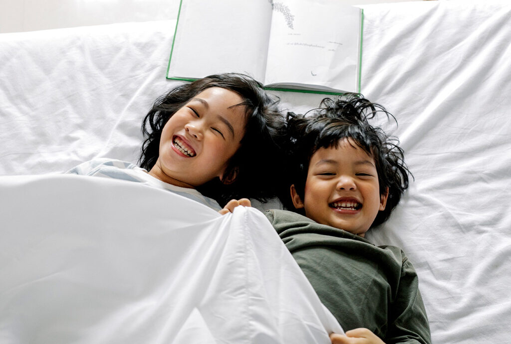 Two kids are laughing with bright smiles and chilling out under a blanket, next to a story book. They radiate having a good time.
