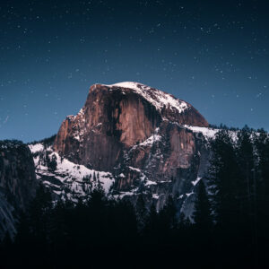 A giant mountain shows up behind a forest whereas the night is starry.